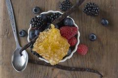 Baies, gousse de vanille et nid d'abeilles sur la surface en bois Images libres de droits