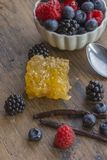 Baies, gousse de vanille et nid d'abeilles sur la surface en bois Image libre de droits