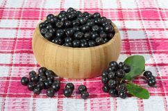 Baies noires de chokeberry dans un plat en bois Images stock