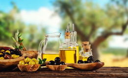 Baies récemment récoltées d'olives en cuvettes en bois et pétrole pressé i Photographie stock libre de droits