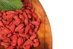 Baies sèches rouges de goji dans un plat Photos libres de droits
