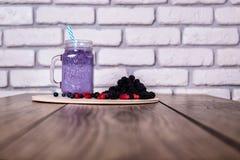 Baies sauvages de smoothie fait maison frais de yaourt dans un pot en verre sur un vieux fond de vintage, plan rapproché, foyer s Photos stock