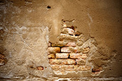 Baige wall. Red brick shown where plaster fell off Royalty Free Stock Photography