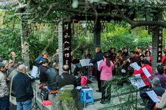 Baihuatan Park, Chengdu, China: Old people rehearse a song in a pavilion, enjoy their retirement. A group of retired people get together rehearse a song at park royalty free stock photography