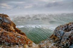 Baikal湖和岩石在12月寒冷 结冰的时期 冰川在水游泳 免版税库存图片