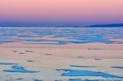 Baikal湖蓝色冰在桃红色日落天空下 免版税库存照片