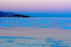 Baikal湖蓝色冰在桃红色日落天空下 图库摄影