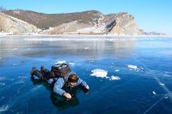 Baikal湖,俄罗斯, 2017年3月, 13日 女性旅游说谎在冰和看通过在湖的底部的冰在O附近的 免版税库存照片