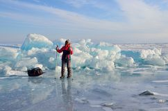 Baikal湖,俄罗斯, 2017年3月, 01日 有爬犁阻力的旅客在冰土坎前面耙松在Bolshie附近K村庄  免版税库存图片