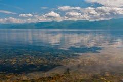 Baikal λίμνη με ακόμα το νερό και τα σύννεφα Στοκ Εικόνες