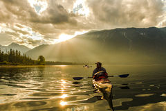 The man in the boat at sunset. The man in a kayak on Lake Baikal stock image