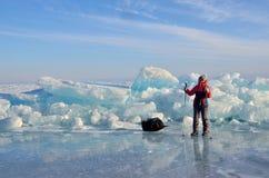 Baikal jezioro, Rosja, Marzec, 01, 2017 Podróżnik z włóczydłem iść przed lodowymi graniami blisko wioski Bolshie Kot Zdjęcia Stock