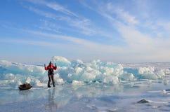 Baikal jezioro, Rosja, Marzec, 01, 2017 Podróżnik z włóczydłem iść przed lodowymi graniami blisko wioski Bolshie Kot Zdjęcie Stock
