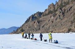 Baikal jezioro, Rosja, Marzec, 01, 2017 Turyści iść z sania na jeziornym Baikal Teren między Bolshoy Kadilny przylądkiem Zdjęcie Stock