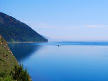 Baikal lake. Mountains, motor boat in the middle of a lake Stock Photos