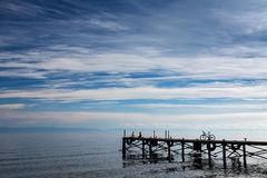 Baikal lake with blue sky and white clouds. Dock with people and bike on the blue sky background Royalty Free Stock Images