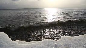 Baikal lake in December with waves and sun. Baikal lake in December with waves, sun and frozen shore stock video footage