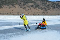 Baikal lake, Russia, March, 01, 2017. Tourists pull each other on a sled in front of the ice ridges near the village of Bolshie Ko Stock Photography