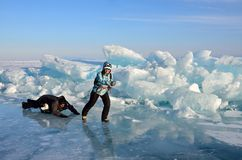 Baikal lake, Russia, March, 01, 2017. Tourists pull each other on a sled in front of the ice ridges near the village of Bolshie Ko Royalty Free Stock Photo