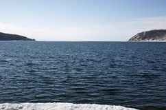 Baikal lake spring landscape view. Snow-covered shore of the lake. Rocky forested coastline. Baikal lake spring landscape view. Snow-covered shore of the lake Stock Photo