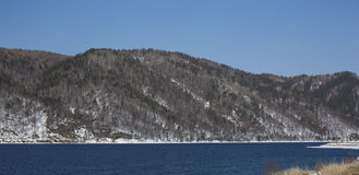 Baikal lake spring landscape view. Snow-covered shore of the lake. Rocky forested coastline. Baikal lake spring landscape view. Snow-covered shore of the lake Royalty Free Stock Photography