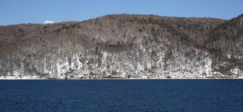 Baikal lake spring landscape view. Snow-covered shore of the lake. Rocky forested coastline. Baikal lake spring landscape view. Snow-covered shore of the lake Royalty Free Stock Photos
