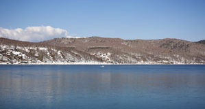 Baikal lake spring landscape view. Snow-covered shore of the lake. Rocky forested coastline. Baikal lake spring landscape view. Snow-covered shore of the lake Royalty Free Stock Image