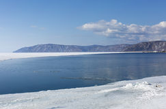 Baikal lake spring landscape view. Snow-covered shore of the lake. Rocky forested coastline. Boundary of ice and open. Water Stock Photos