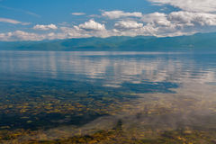 Baikal lake with still water and clouds. View of lake Baikal with white clouds Stock Images