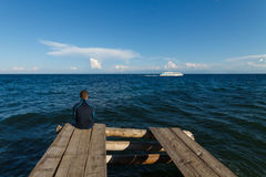 Baikal lake view. Man sitting on old wooden dock with Baikal lake view royalty free stock photos