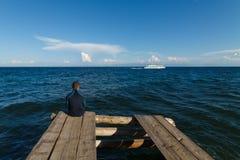 Baikal lake view. Man sitting on old wooden dock with Baikal lake view Royalty Free Stock Photos