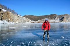 Baikal See, Russland, März, 13, 2017 Russland, Olkhon-Insel Tourist, der auf Baikal-Eis im März eisläuft Lizenzfreie Stockbilder