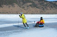 Baikal sjö, Ryssland, mars, 01, 2017 Turister drar sig på en släde framme av iskanterna nära byn av bolsjeviken Ko Arkivbild