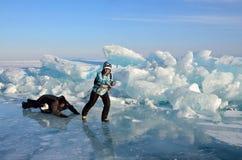 Baikal sjö, Ryssland, mars, 01, 2017 Turister drar sig på en släde framme av iskanterna nära byn av bolsjeviken Ko Royaltyfri Foto