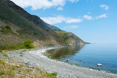 Baikal stony beach with sun and blue water Stock Photos