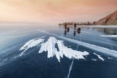 Baikal w zimie, dwa podróżnika iść na lodzie przy zmierzchem obraz stock