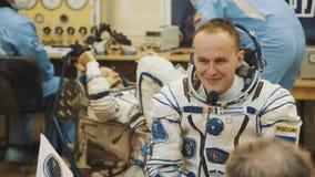 BAIKONUR KASAKHSTAN - JULE 28: Tre levande verkliga kosmonaut går till raket, säger farväl till en folkmassa av folk, våg arkivfilmer