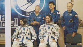 BAIKONUR, KAZACHSTAN - JULE 28: Drie leven echte kosmonauten gaan naar de raket, zeggen vaarwel aan een menigte van mensen, golf stock video