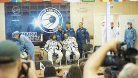 BAIKONUR, KAZACHSTAN - JULE 28: Drie leven echte kosmonauten gaan naar de raket, zeggen vaarwel aan een menigte van mensen, golf stock videobeelden