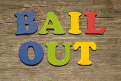 Bail out. Text on a wooden background stock photos