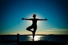 Bailado da silhueta da jovem mulher com os braços abertos que dançam ao mar Fotografia de Stock