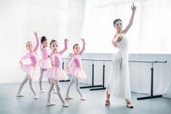 bailado praticando do professor novo com as crianças adoráveis no rosa fotografia de stock royalty free
