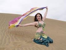 Bailarín árabe con un paño del color en el desierto Fotografía de archivo