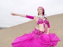 Bailarín árabe en las dunas con la espada imágenes de archivo libres de regalías