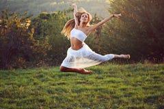 Bailarín clásico hermoso que salta en luz de la puesta del sol Imagen de archivo
