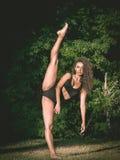 Bailarín con la pierna aumentada en un bosque Foto de archivo