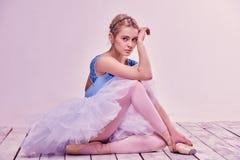 Bailarín de ballet cansado que se sienta en el piso de madera Imágenes de archivo libres de regalías