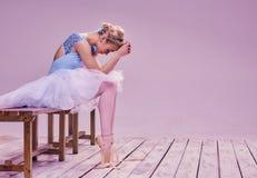 Bailarín de ballet cansado que se sienta en el piso de madera Fotografía de archivo libre de regalías