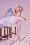 Bailarín de ballet cansado que se sienta en el piso de madera Foto de archivo libre de regalías