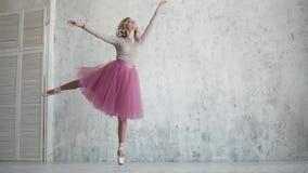 Bailarín de ballet en un tutú rosado y zapatos del pointe bailarina joven hermosa en un ensayo ligereza y tolerancia del almacen de metraje de vídeo